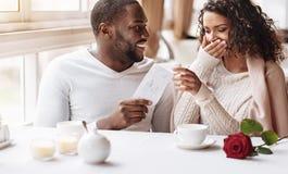 Ευχαριστημένη γυναίκα αφροαμερικάνων που λαμβάνει ένα παρόν από το φίλο της στοκ εικόνα