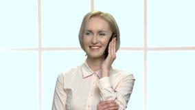 Ευχαριστημένη γυναίκα γραφείων που μιλά στο τηλέφωνο κυττάρων απόθεμα βίντεο