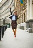 Ευχαριστημένη επιχειρησιακή γυναίκα που πηδά για τη χαρά μιλώντας στο sm Στοκ Εικόνες