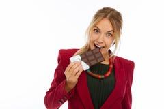 Ευχαριστημένη εύθυμη νέα γυναίκα που δαγκώνει τη σοκολάτα της στοκ φωτογραφία με δικαίωμα ελεύθερης χρήσης
