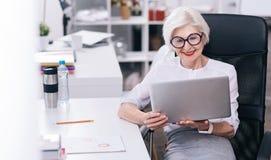 Ευχαριστημένη ηλικίας επιχειρησιακή κυρία που χρησιμοποιεί τη συσκευή στην εργασία Στοκ Εικόνα