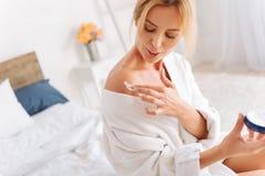 Ευχαριστημένη νέα γυναίκα που εφαρμόζει την κρέμα στον ώμο Στοκ εικόνα με δικαίωμα ελεύθερης χρήσης