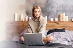 Ευχαριστημένη νέα γυναίκα που χρησιμοποιεί το lap-top στο σπίτι στοκ φωτογραφία με δικαίωμα ελεύθερης χρήσης
