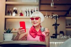 Ευχαριστημένη συμπαθητική ηλικίας γυναίκα που κρατά ένα φλυτζάνι καφέ στοκ εικόνα