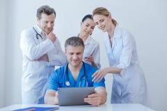 Ευχαριστημένοι γιατροί που απολαμβάνουν τη νέα ψηφιακή συσκευή στην εργασία Στοκ εικόνα με δικαίωμα ελεύθερης χρήσης