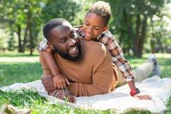 Ευχαριστημένοι συμπαθητικοί πατέρας και γιος που στηρίζονται μαζί στο πάρκο στοκ φωτογραφίες