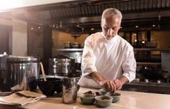 Ευχαριστημένος γενειοφόρος αρχιμάγειρας που παίρνει τα καρυκεύματα για το μαγείρεμα στοκ φωτογραφίες