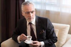 Ευχαριστημένος γενειοφόρος καφές κατανάλωσης επιχειρηματιών στο ξενοδοχείο στοκ εικόνες