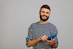 Ευχαριστημένος γενειοφόρος νεαρός άνδρας που χρησιμοποιεί τις πιό πρόσφατες συσκευές στοκ εικόνες