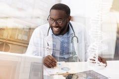 Ευχαριστημένος γιατρός που εργάζεται με τις σημειώσεις στοκ φωτογραφία