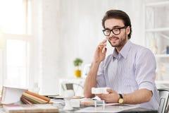 Ευχαριστημένος διευθυντής που συζητά την εργασία για το τηλέφωνο στοκ φωτογραφία