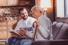 Ευχαριστημένος εθελοντής που διαβάζει ένα βιβλίο για έναν συνταξιούχο στοκ φωτογραφίες