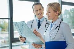Ευχαριστημένος ελκυστικός γιατρός που εξετάζει τη φωτογραφία ακτίνας X στοκ εικόνα με δικαίωμα ελεύθερης χρήσης