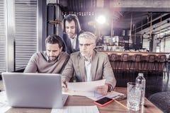 Ευχαριστημένος επιχειρηματίας που κοιτάζει επίμονα στην οθόνη του lap-top στοκ εικόνες