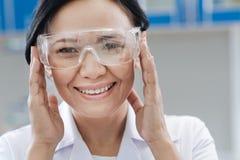 Ευχαριστημένος εργαστηριακός επιστήμονας που καθορίζει τα προστατευτικά γυαλιά της Στοκ Φωτογραφίες