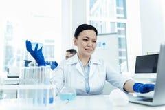 Ευχαριστημένος ερευνητής που κάνει μια δοκιμή στο εργαστήριο στοκ φωτογραφίες