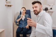 Ευχαριστημένος ευχάριστος γιατρός που δείχνει στο διάγραμμα ματιών στοκ εικόνες
