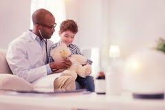 Ευχαριστημένος εύθυμος αρσενικός γιατρός που θεραπεύει τον ασθενή του στοκ εικόνες