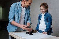 Ευχαριστημένος εύθυμος πατέρας που δείχνει στο αποσυντεθειμένο πυροβόλο όπλο Στοκ Εικόνες