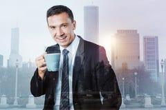 Ευχαριστημένος θετικός επιχειρηματίας που απολαμβάνει το τσάι του στοκ φωτογραφίες με δικαίωμα ελεύθερης χρήσης