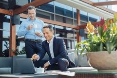 Ευχαριστημένος θετικός επιχειρηματίας που δείχνει στην οθόνη lap-top στοκ φωτογραφία