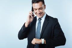 Ευχαριστημένος θετικός επιχειρηματίας που ελέγχει το χρόνο στοκ εικόνα