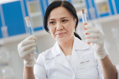 Ευχαριστημένος θετικός φαρμακοποιός που εξετάζει τους σωλήνες δοκιμής στοκ εικόνες με δικαίωμα ελεύθερης χρήσης