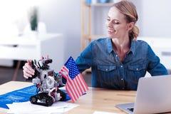 Ευχαριστημένος θηλυκός μηχανικός που εξετάζει το ρομπότ στοκ φωτογραφία