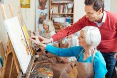 Ευχαριστημένος καλλιτέχνης που βοηθά την ηλικιωμένη γυναίκα στη ζωγραφική του στούντιο στοκ εικόνα