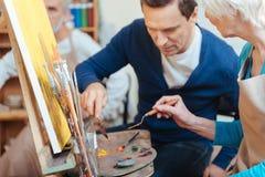 Ευχαριστημένος καλλιτέχνης που βοηθά την ηλικιωμένη γυναίκα στη ζωγραφική στοκ φωτογραφία με δικαίωμα ελεύθερης χρήσης