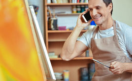 Ευχαριστημένος καλλιτέχνης που χρησιμοποιεί το κινητό τηλέφωνο στη ζωγραφική του στούντιο στοκ εικόνα