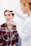 Ευχαριστημένος καλλυντικός χειρούργος που κρατά το πρόσωπο ασθενών της στοκ εικόνες