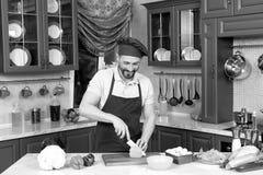Ευχαριστημένος μάγειρας που τεμαχίζει το φρέσκο πιπέρι στον πίνακα κουζινών στοκ εικόνα