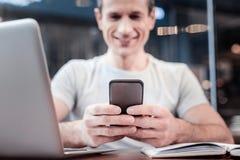 Ευχαριστημένος νεαρός άνδρας που εξετάζει το τηλέφωνό του Στοκ Φωτογραφίες