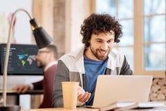 Ευχαριστημένος νεαρός άνδρας που εργάζεται στο lap-top του στοκ φωτογραφία με δικαίωμα ελεύθερης χρήσης