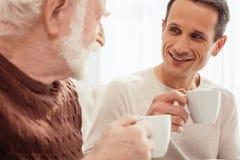 Ευχαριστημένος νεαρός άνδρας που μιλά με το grandpa του στοκ φωτογραφία με δικαίωμα ελεύθερης χρήσης