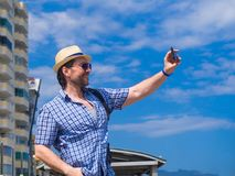 Ευχαριστημένος νεαρός άνδρας στον καθιερώνοντα τη μόδα ελεγμένο χρόνο εξόδων πουκάμισων υπαίθριο, εξερευνώντας τα περίχωρα το πρω στοκ φωτογραφία