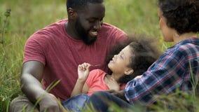 Ευχαριστημένος πατέρας που κρατά λίγη κόρη και που παίζει με τη σγουρή τρίχα της, προσοχή στοκ εικόνες