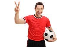 Ευχαριστημένος ποδοσφαιριστής που κάνει μια χειρονομία νίκης στοκ εικόνα