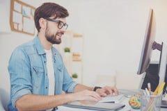 Ευχαριστημένος προγραμματιστής στα γυαλιά που χρησιμοποιούν έναν υπολογιστή στοκ φωτογραφίες με δικαίωμα ελεύθερης χρήσης