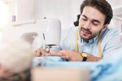 Ευχαριστημένος ράφτης που εργάζεται σε μια ράβοντας μηχανή στοκ φωτογραφία