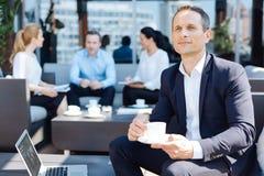 Ευχαριστημένος στοχαστικός επιχειρηματίας που απολαμβάνει το espresso του στοκ φωτογραφία