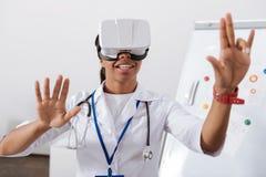 Ευχαριστημένος συμπαθητικός γιατρός σχετικά με την εικονική οθόνη στοκ εικόνα με δικαίωμα ελεύθερης χρήσης