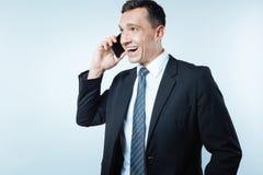 Ευχαριστημένος συμπαθητικός επιχειρηματίας που έχει μια τηλεφωνική συνομιλία στοκ εικόνες με δικαίωμα ελεύθερης χρήσης