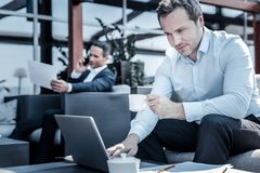 Ευχαριστημένος συμπαθητικός επιχειρηματίας που χρησιμοποιεί το lap-top στοκ εικόνα με δικαίωμα ελεύθερης χρήσης