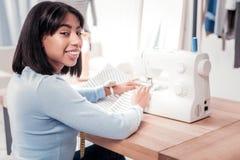 Ευχαριστημένος σχεδιαστής που γυρίζει σε σας ράβοντας ένα φόρεμα στοκ εικόνες