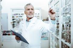Ευχαριστημένος φαρμακοποιός που εργάζεται στο φαρμακείο με την ευχαρίστηση στοκ φωτογραφία