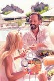 Ευχαριστημένος φροντίζοντας πατέρας που ταΐζει την κόρη του με τα τρόφιμα στοκ εικόνα με δικαίωμα ελεύθερης χρήσης