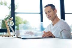 Ευχαριστημένος όμορφος επιχειρηματίας που είναι στην εργασία στοκ φωτογραφία με δικαίωμα ελεύθερης χρήσης