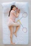 Ευχαριστημένος όμορφος ύπνος γυναικών κοντά στις ρακέτες μπάντμιντον στοκ εικόνες